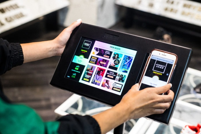 Customers at Jimmy Jazz can sign up for the Fresh Selects Loyalty Program using their phone. Then the phone interacts with the tablet, showcasing additional information or displaying the customer's rewards.