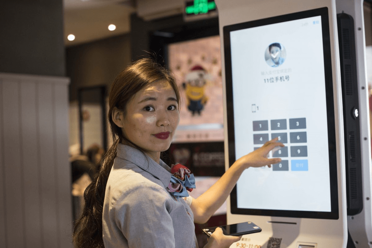 Restaurant worker at the Chinese KFC showing how their facial recognition system works